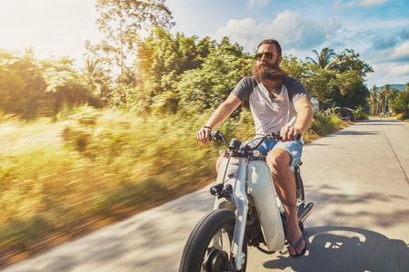 driving vintage motorbike fast through country side in thailand photo