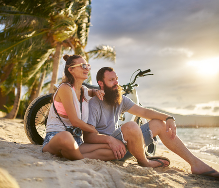 island: romantic couple couple with motorbike in thailand watching sunset Stock Photo