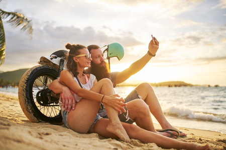 romantic tourist couple in thailand taking selfies on beach by motorbike Foto de archivo