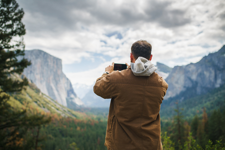 man in brown coat taking photo of yosemite with smartphone