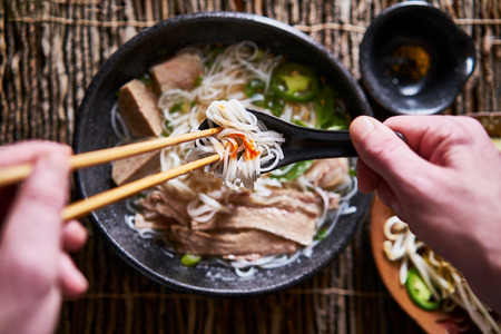 top down composition of eating vietnamese pho with chopsticks and spoon, has dab of sriracha for flavor Banque d'images