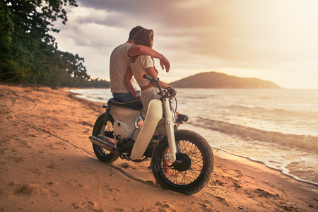 romantic love: romantic couple sitting on vintage bike watching sunset at koh samui thailand