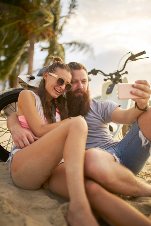 romantic tourist couple in thailand taking selfies on beach by motorbike Stock Photo