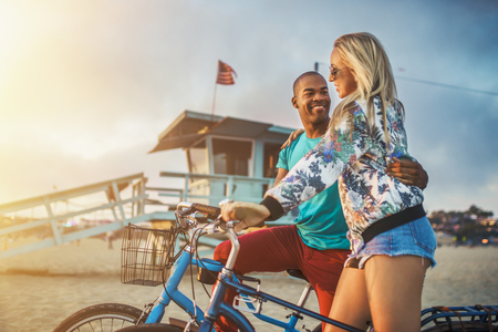 woman sunset: romantic couple watch sunset on santa monica beach after bike ride