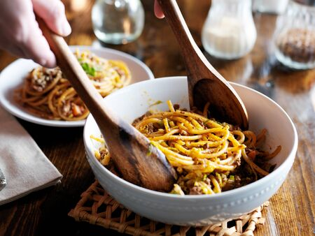 serving spaghetti with wooden spoons out of bowl