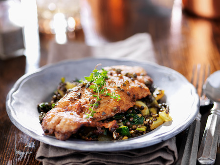 prepared dish: fried catfish on black lentils with capers and thyme Stock Photo
