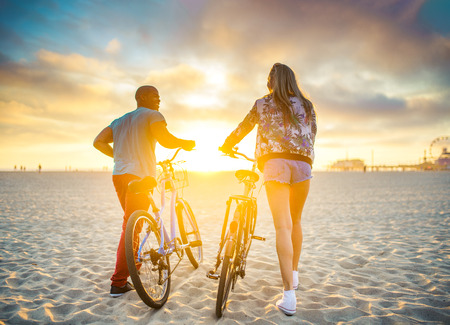 freedom: couple walking bikes together on beach to stunning sunset