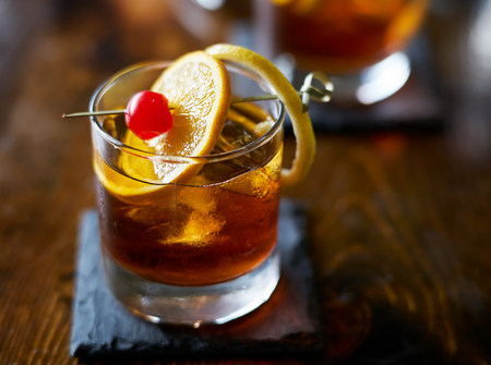 old fashioned cocktail garnished with cherry, orange and lemon peel
