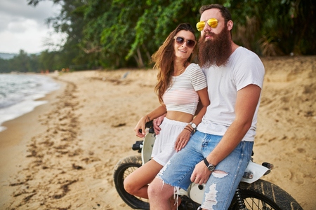 expat couple sitting on vintage bike on thai beach