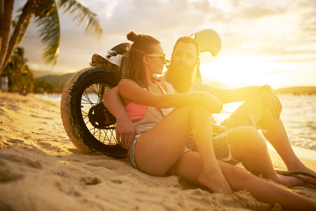 island: couple in thailand with motorbike watching sunset together
