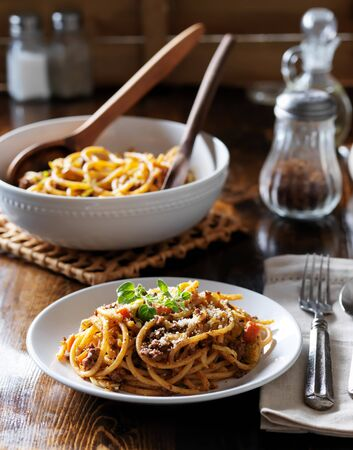 rustic spaghetti and beef dinner with serving bowl in background
