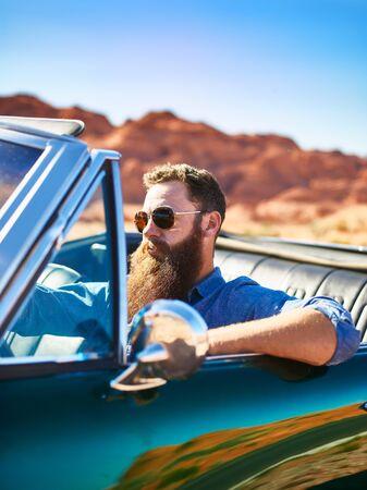 bearded guy in desert sitting in cool vintage car