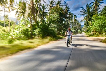 Treibende weinlese motorrad schnell durch landseite in thailand photo