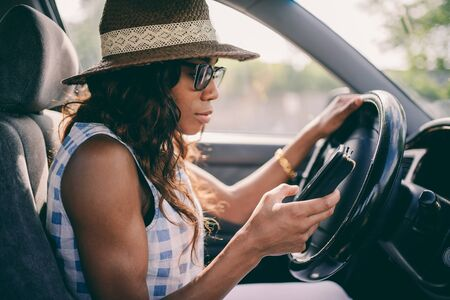 Woman Using Mobile Phone While Driving Car with low contrast filter Stock Photo