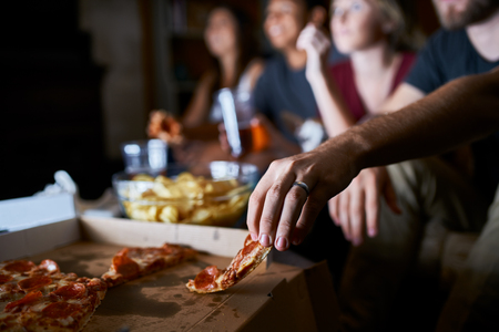 close up of man picking up slice of pizza at party