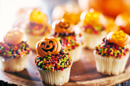 festive halloween pumpkin cupcakes with chocolate frosting and colorful sprinkles