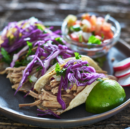 colorful plate of three mexican carnitas street tacos with cilantro and red cabbage Stock fotó
