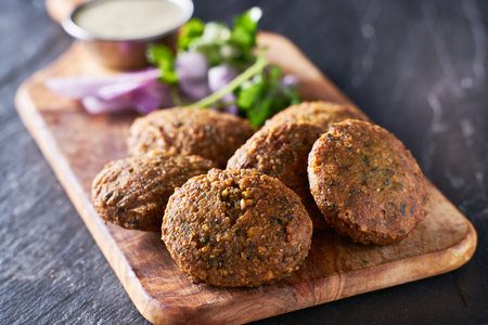 tasty falafel pieces on wooden bread board Фото со стока
