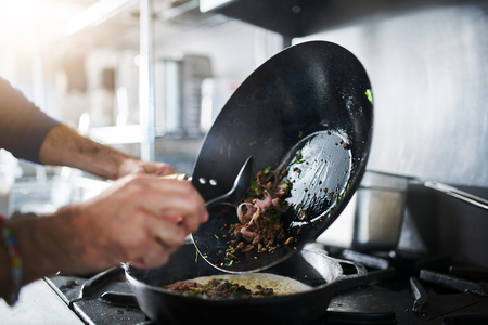 chef cooking food in wok and pouring it onto wrap in iron skillet Archivio Fotografico