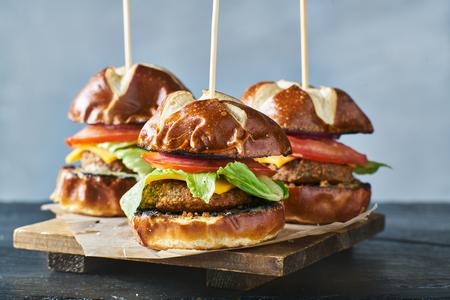 three vegan burger sliders with pretzel buns