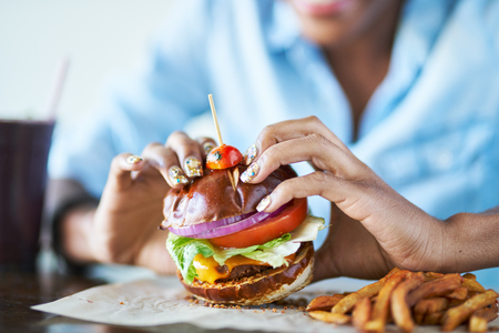 close up of african american woman about to eat vegan meatless cheese burger at restaurant