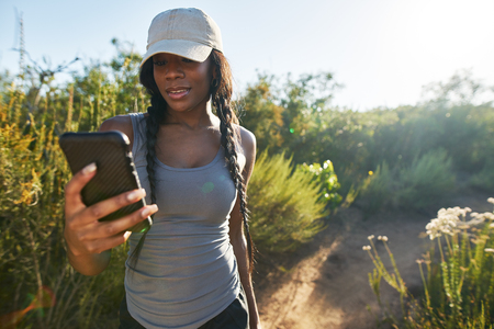 female african american hiker looking at smartphone while taking a break from walking