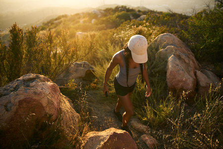 fit female african american hiker walking up rocky path on mountain with san diego in background below Stock Photo