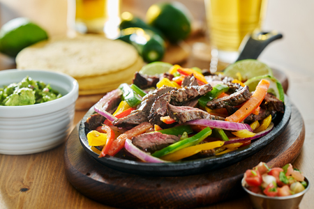 mexican beef fajitas in iron skillet with guacamole and beer Stock Photo