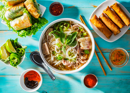 vietnamese beef pho bo soup in bowl on table top with spring rolls and appetizers 版權商用圖片 - 118110979