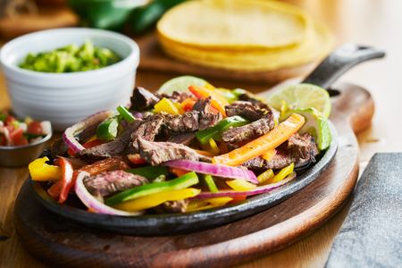 mexican beef fajitas in iron skillet with bell peppers and guacamole on the side 스톡 콘텐츠