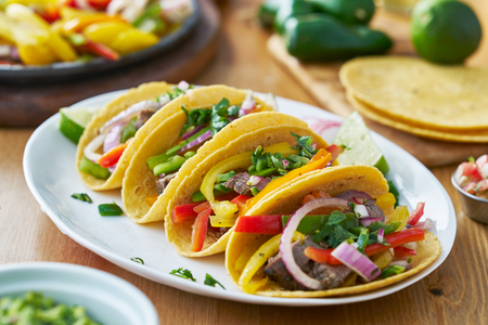 tacos with beef and bell pepper filling served with guacamole