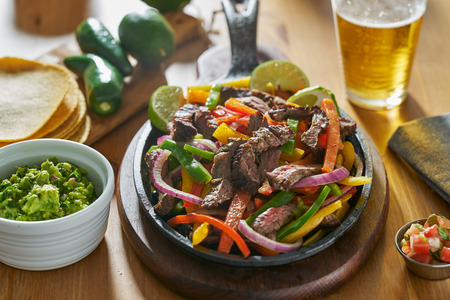mexican beef fajitas in iron skillet with guacamole and beer Stock fotó - 118468147