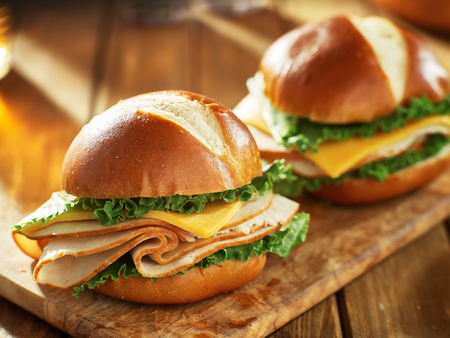 two cold cut style turkey and cheese sandwiches on pretzel buns