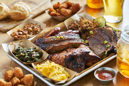 texas style bbq tray with smoked brisket, st louis ribs, pulled pork, chicken, hot links, and sides Stock Photo