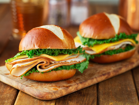 two turkey and cheese sandwiches on pretzel buns Stock Photo