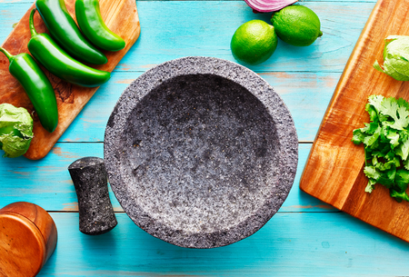 empty molcajete on table with ingredients ready to prep Stock Photo