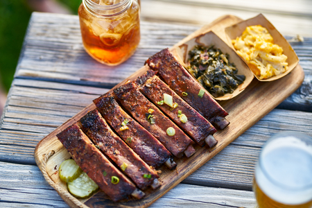 st louis style bbq ribs with collard greens and mac & cheese outside on picnic table during sunny summer day Stok Fotoğraf - 118468796