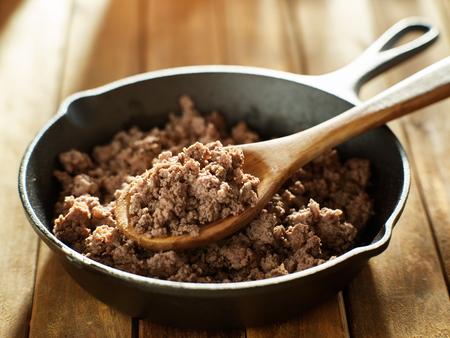 cucharada de carne molida recién cocida de una sartén de hierro