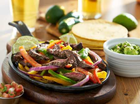 mexican beef fajitas in iron skillet with guacamole and beer Stockfoto
