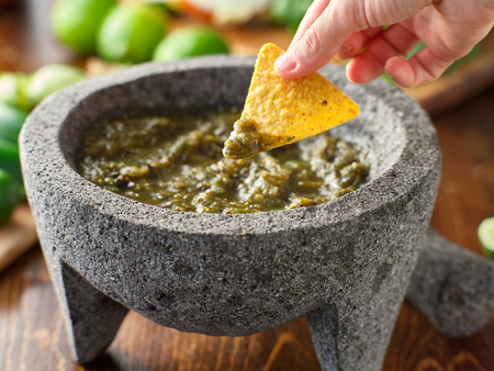 dipping a tortilla chip in mexican salsa verde Stock Photo