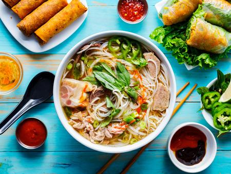 Colorido pho bo vietnamita con carne y rollitos de primavera