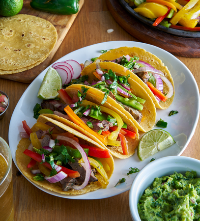 mexican fajita tacos in yellow corn tortilla served with guacamole