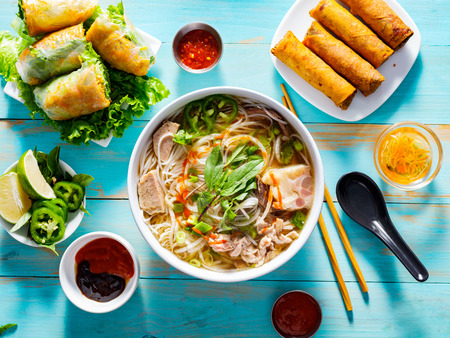 vietnamese pho bo soup with appetizers on table and drizzled with sriracha sauce 版權商用圖片 - 118469272