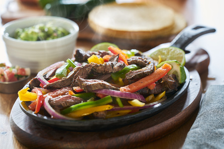 steaming hot mexican beef fajitas in iron skillet with bell peppers and guacamole on the side 스톡 콘텐츠