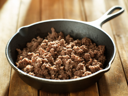 freshly browned ground beef in iron skillet on wooden table top Stockfoto