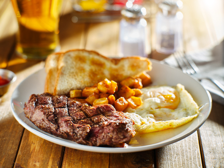 steak and eggs breakfast with toast and homestyle potatoes in restaurant