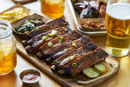 st louis style bbq ribs on table top with sweet tea, beer, collard greens and mac & cheese