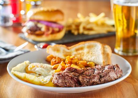 Desayuno de bistec y huevos con tostadas y patatas caseras en restaurante. Foto de archivo
