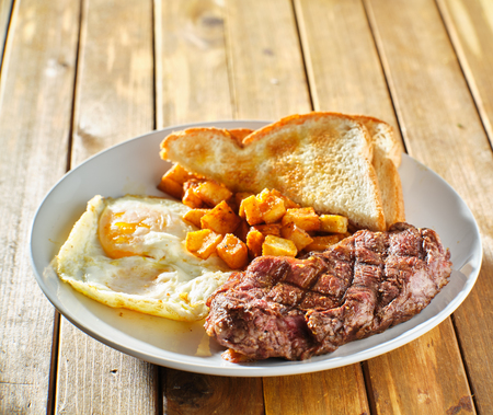 steak and eggs breakfast with toast and homestyle potatoes on wooden table