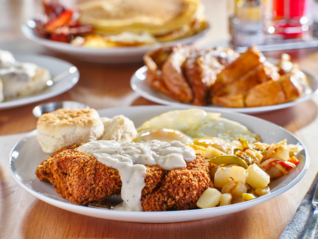 chicken fried steak covered in gravy with sunny side up eggs and breakfast foods at restaurant Reklamní fotografie